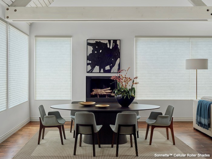 A dining room with black and white painting and a black vase.